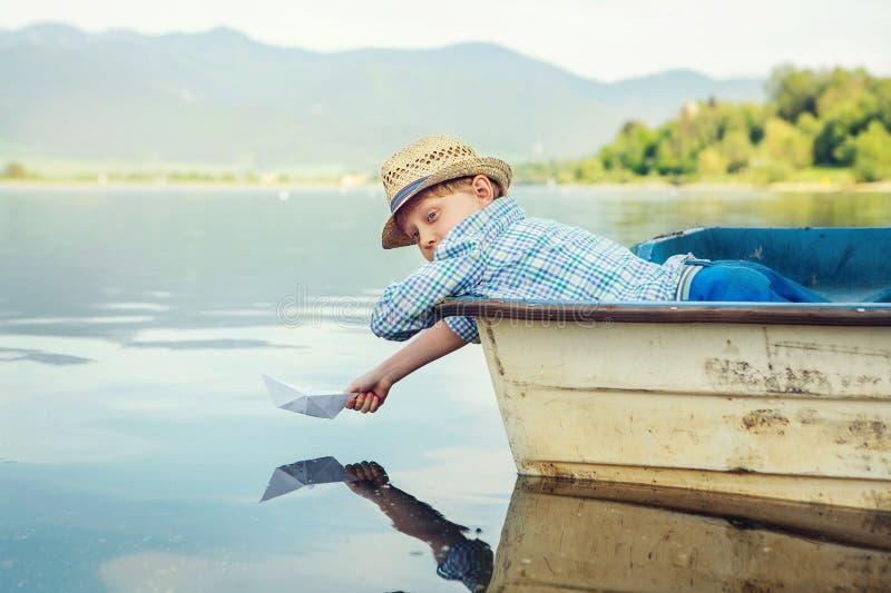 Bateau de papier de lancement de petit garçon se situant dans le vieux bateau images stock