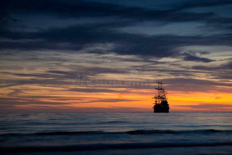 Bateau de pirate dans le paysage de coucher du soleil images libres de droits