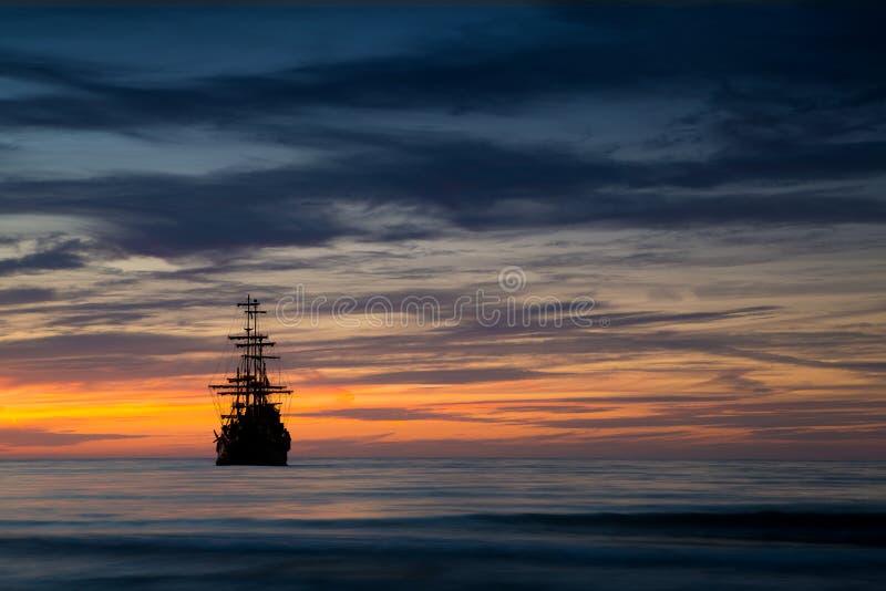 Bateau de pirate dans le paysage de coucher du soleil photographie stock