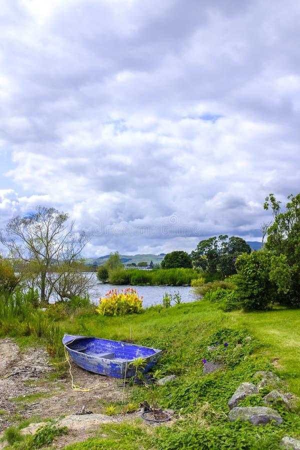 Bateau de rangée abandonné par un lac image stock