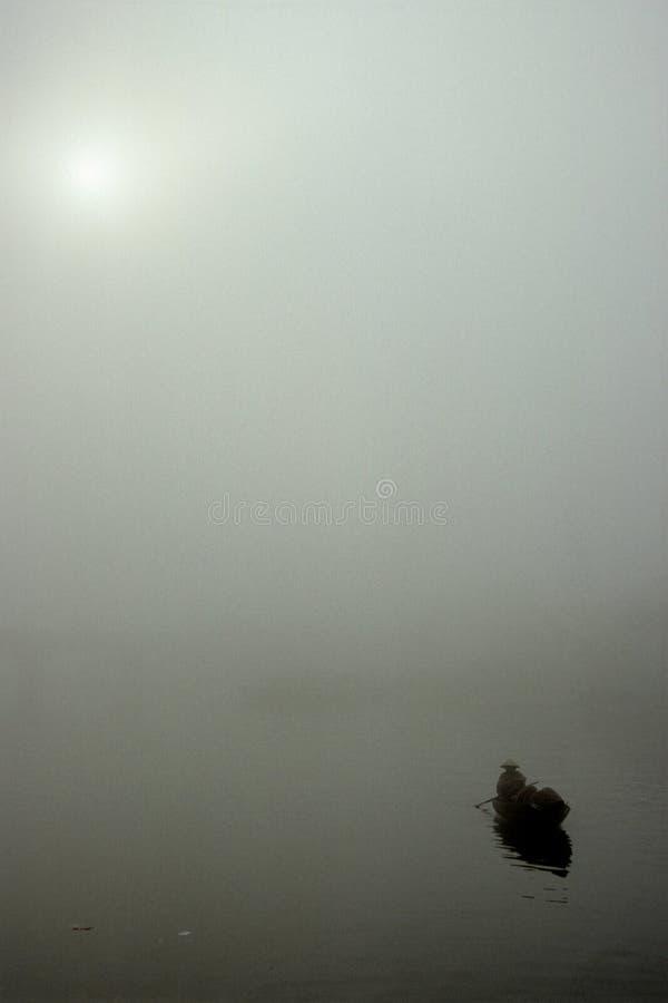 Bateau de rangée solitaire sortant de la brume en Hoi An Vietnam photo stock
