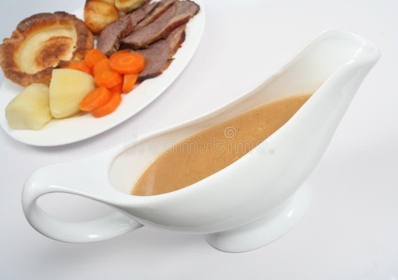Bateau de sauce au jus avec le dîner photo stock