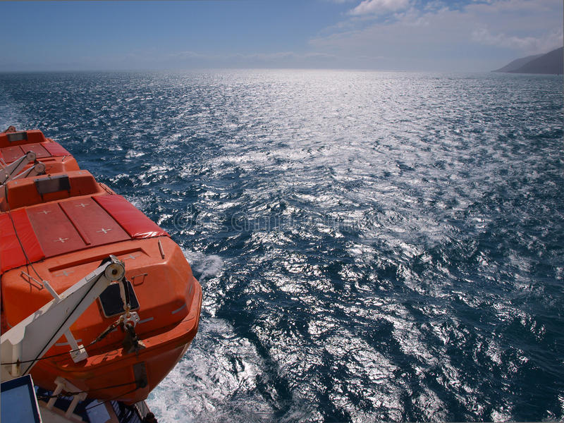 Bateau de sauvetage sur un bac, mer bleue profonde photos stock