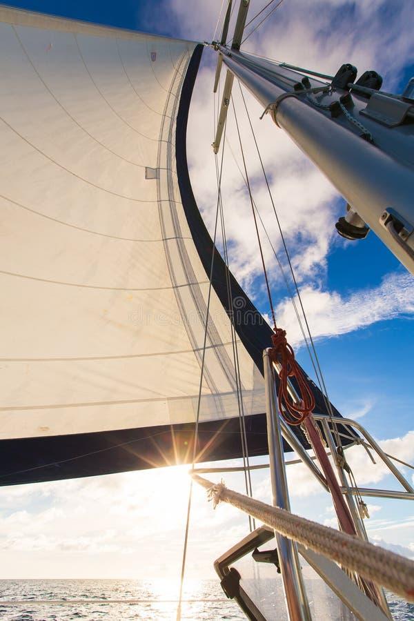Bateau de yacht de navigation sur l'eau d'océan contre le coucher du soleil concept de course photographie stock
