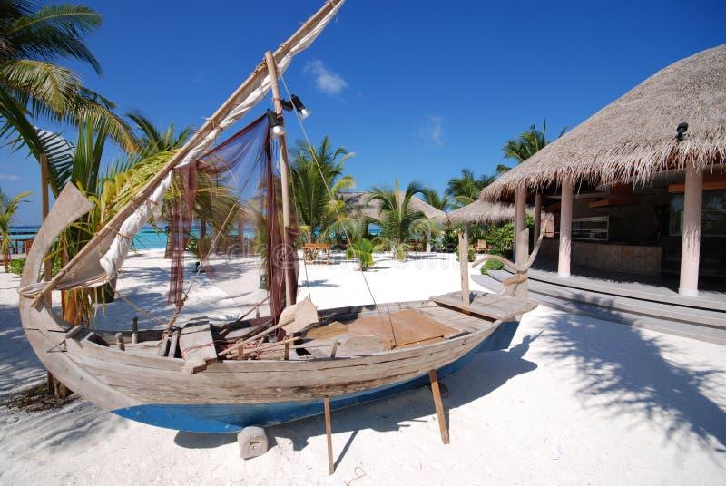 Bateau devant le gril d'atoll photos stock