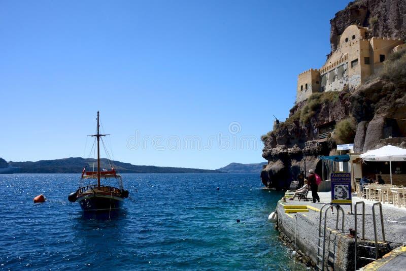 Bateau en bois amarré en mer bleue de Santorini près d'une falaise et d'un bâtiment en pierre photographie stock