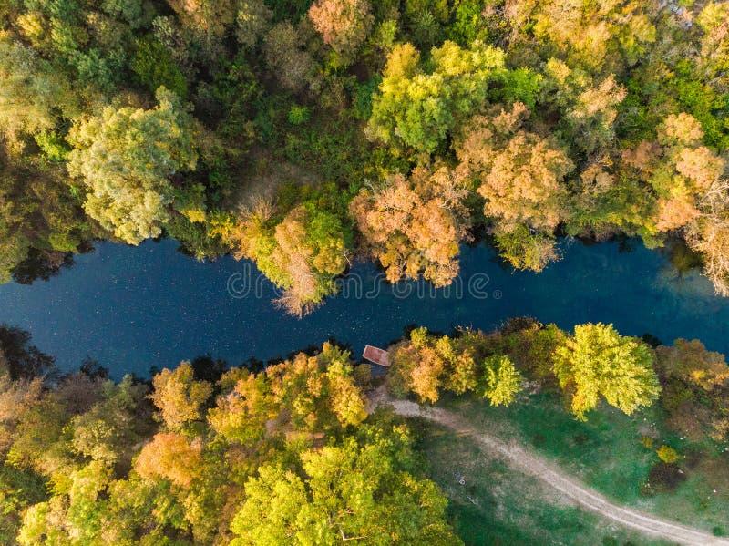 Bateau en bois sur la rivière dans la forêt d'automne image stock