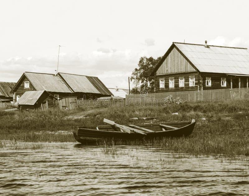 Bateau en bois sur le côté de lac dans le petit village photo libre de droits