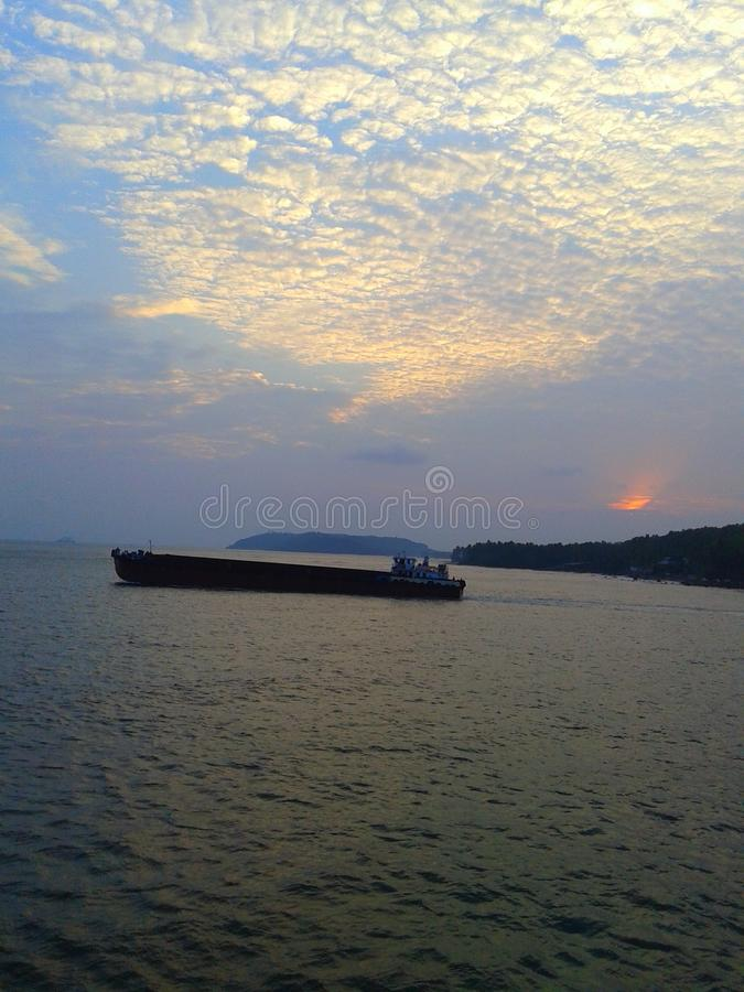 Bateau en mer avec le coucher du soleil image libre de droits