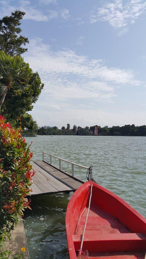 Bateau et pilier rouges dans un lac image stock