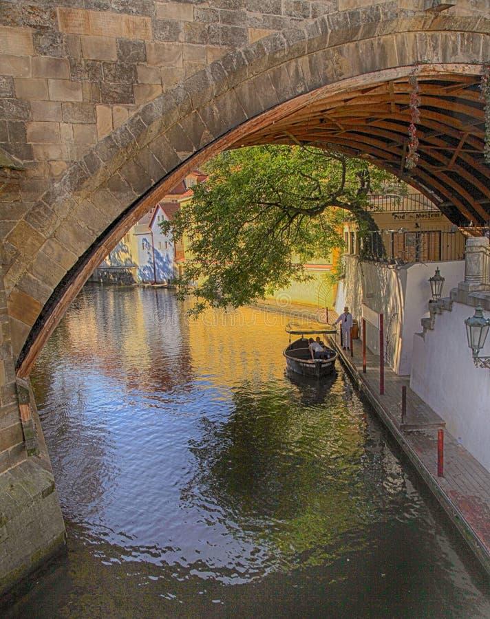 Bateau et vieilles maisons sous Charles Bridge dans le réalisateur étroit de rivière photos stock