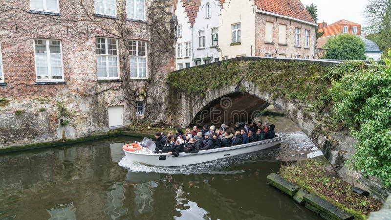 Bateau guidé de touristes sur le canal à Bruges en hiver, Bruges, Belgique image libre de droits
