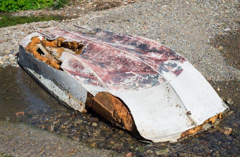 Bateau inversé abandonné se trouvant sur le rivage de la coque endommagée photographie stock