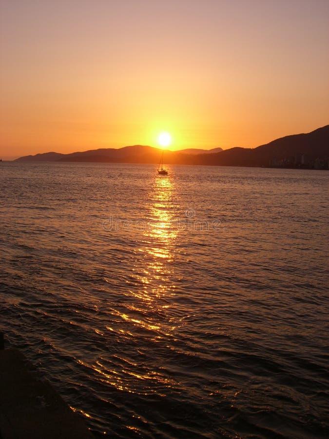 Bateau isolé au coucher du soleil image stock