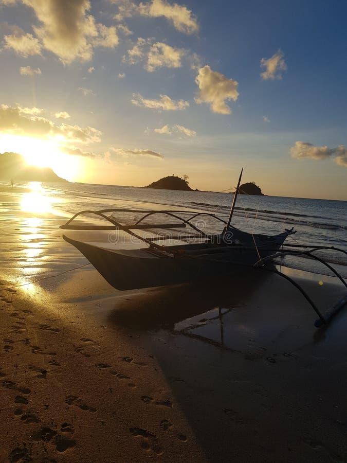 Bateau local en plage de Nacpan avec la plage renversante et le coucher du soleil photographie stock