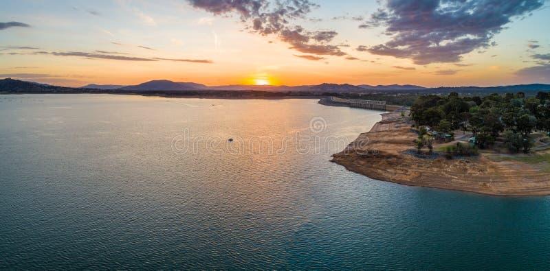 Bateau minuscule dans le grand lac au coucher du soleil image libre de droits