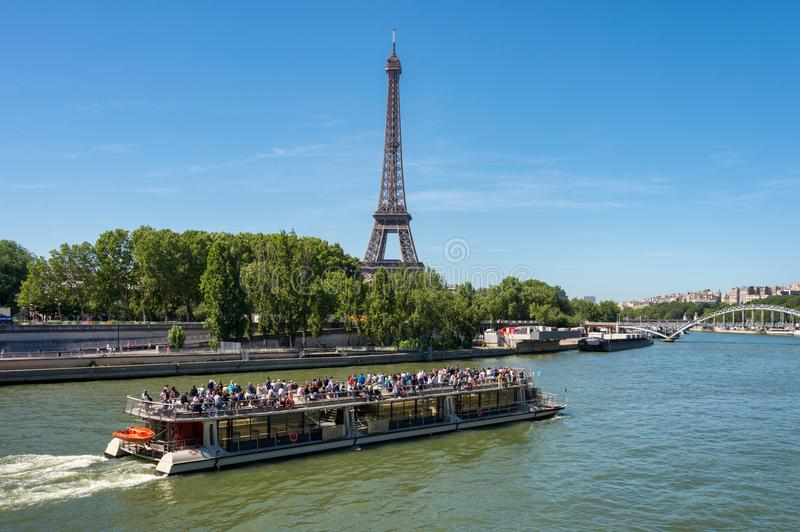 Bateau Mouche on the Seine river with Eiffel Tower in the background royalty free stock images