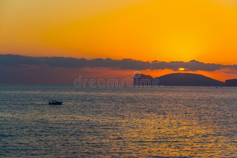 Bateau par le capo Caccia au coucher du soleil image libre de droits