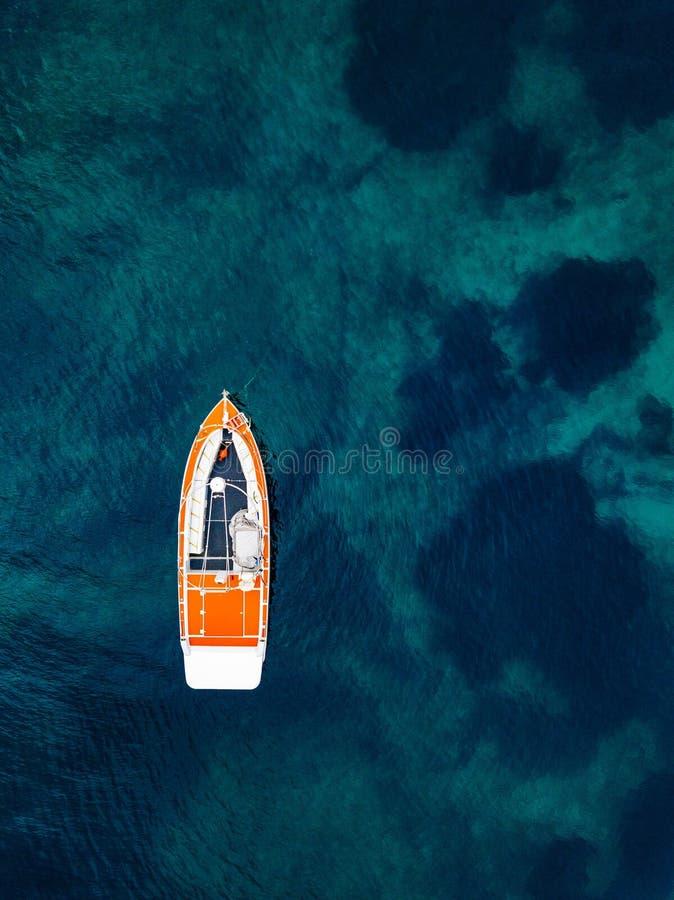 Bateau rouge dans l'eau bleue profonde Silhouette d'homme se recroquevillant d'affaires photos libres de droits