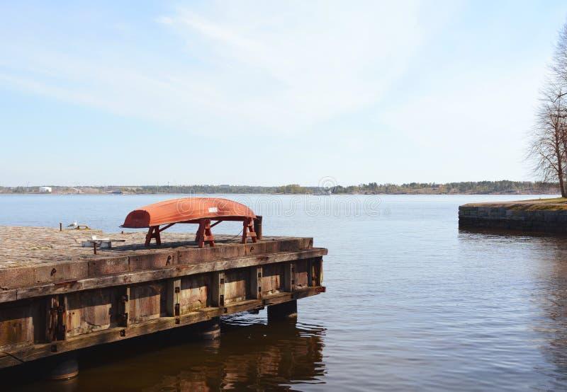 Bateau rouge retourné sur une jetée au-dessus de la mer photographie stock