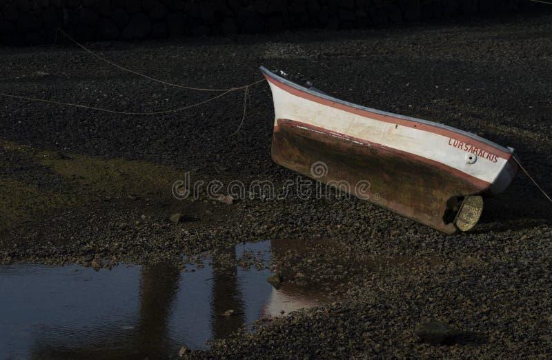 Bateau rouillé à terre à côté de l'eau image libre de droits