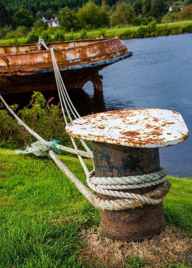 Bateau rouillé fixe dans le port images libres de droits
