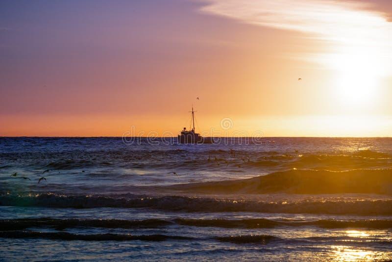Bateau se dirigeant au port, au coucher du soleil, Moss Landing, la Californie photographie stock libre de droits