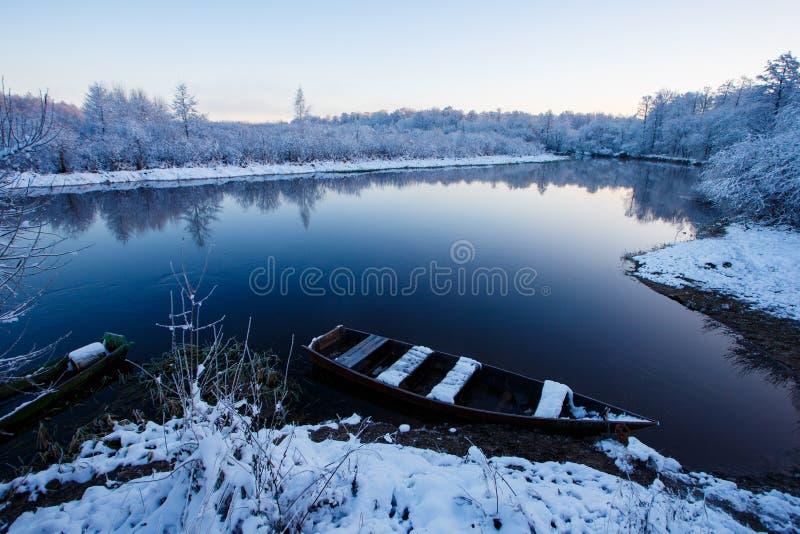 Bateau simple flottant le long de la rivière, de la forêt neigeuse et des buissons image stock