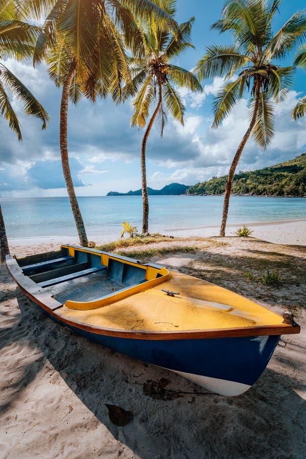 Bateau sous des palmiers de noix de coco le jour ensoleillé sur le rivage de la plage tropicale, îles des Seychelles photographie stock libre de droits