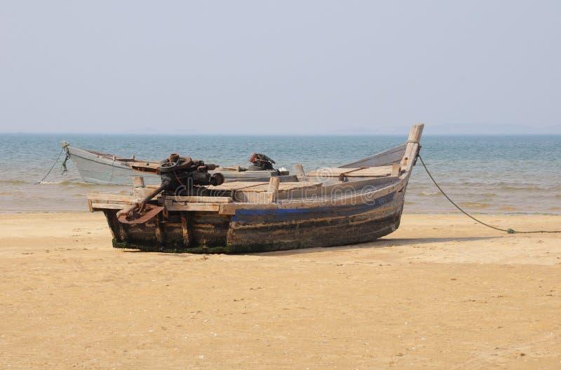 Bateau superficiel par les agents sur une plage images libres de droits