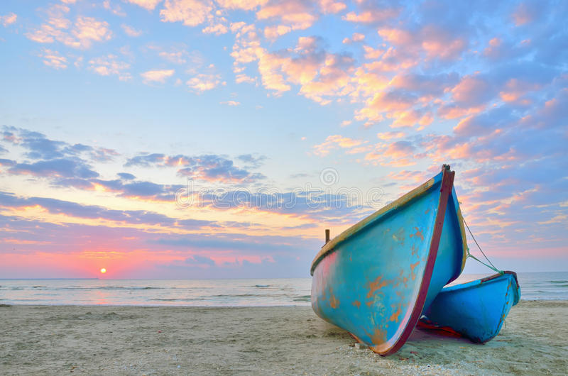 Bateau sur la belle plage dans le lever de soleil photographie stock libre de droits