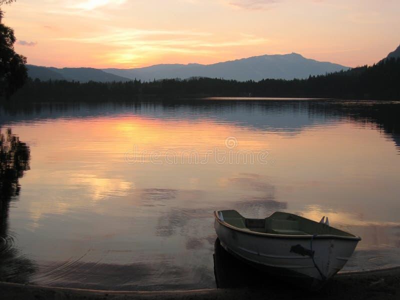 Bateau sur le rivage du lac au coucher du soleil photo stock
