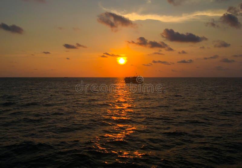 Bateau sur une mer calme dans le coucher du soleil tropical photos stock