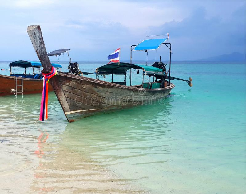 Bateau thaïlandais de longtail sur l'eau verte clair comme de l'eau de roche de turquoise de la plage blanche tropicale célèbre d photos stock