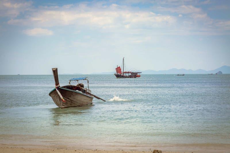 Bateau tha?landais de longtail sur la plage de Phra Nang Allant à la mer, sur le fond d'un bateau de navigation noir avec les voi image stock