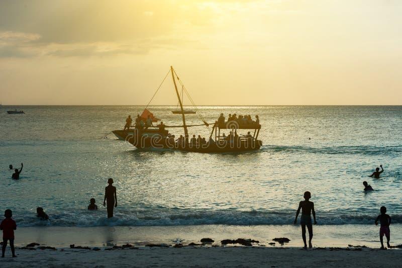 Bateau touristique près de plage de Zanzibar au coucher du soleil image stock