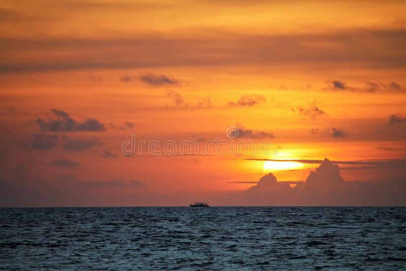 Bateau traditionnel de Dhoni sur l'horizon éloigné avec le coucher du soleil orange en Maldives photo libre de droits