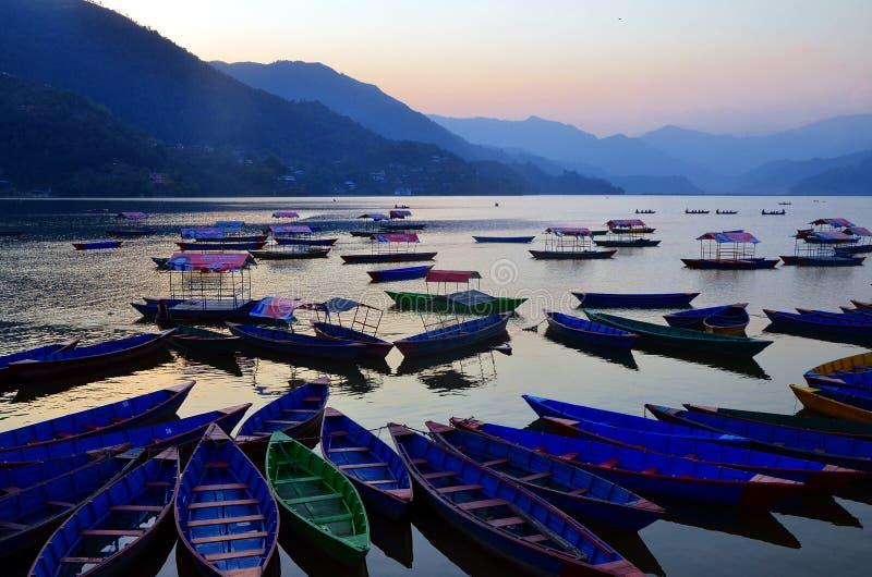 Bateaux à rames et bateaux en bois colorés de ponton au lac Begnas, Pokhara, Népal image stock