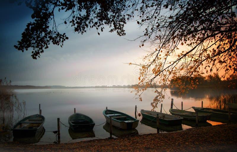 Bateaux à rames sur le rivage de lac avant le lever de soleil, paysage scénique avec l'espace de copie, foyer choisi images libres de droits
