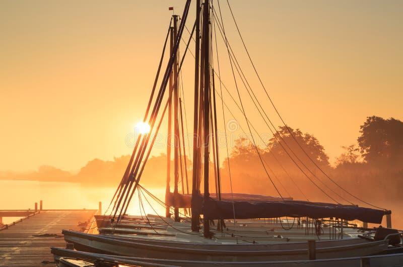 Bateaux à voile au lever de soleil photographie stock libre de droits