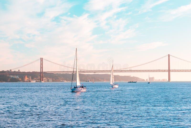 Bateaux à voile flottant sur la baie de mer contre le contexte d'un grand pont en fer, d'un ciel bleu et d'un coucher du soleil images stock