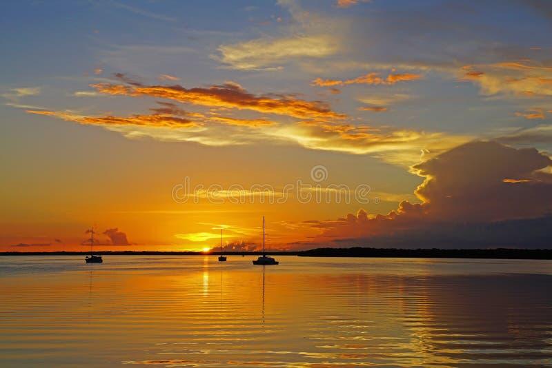 Bateaux à voile se reflétant dans l'océan calme pendant un coucher du soleil photo stock
