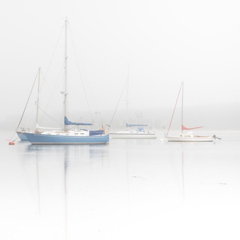 Bateaux à voile sur le lac brumeux photo stock