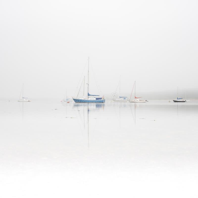 Bateaux à voile sur le lac brumeux image stock