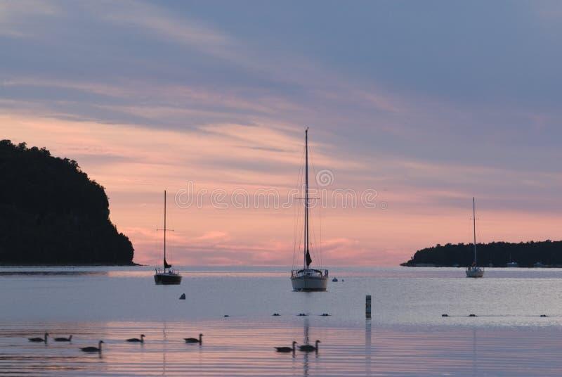 Bateaux à voiles au coucher du soleil photos stock