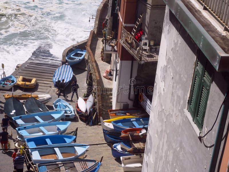 Bateaux éditoriaux sur le bord de mer Riomaggiore, Cinque Terre, Italie de trottoir photos libres de droits