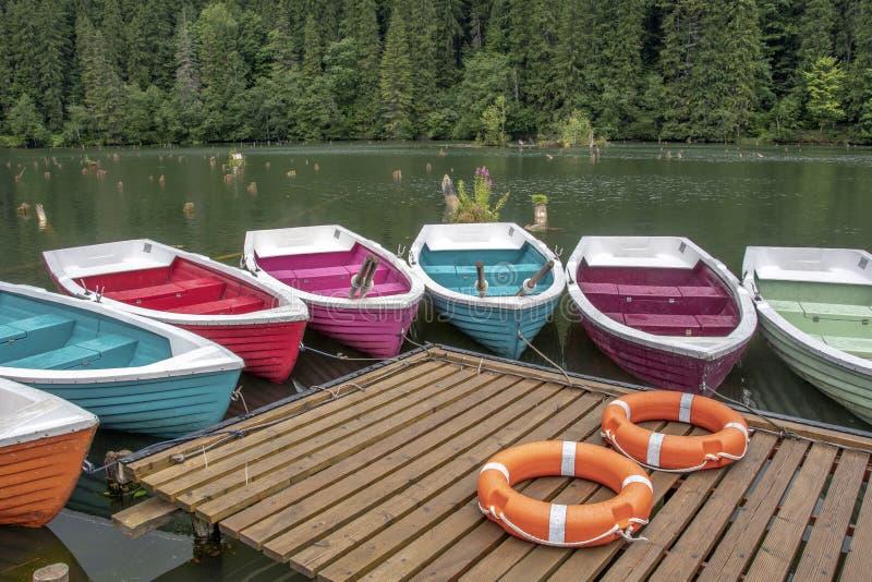 Bateaux colorés dans le lac rouge en Roumanie photos stock