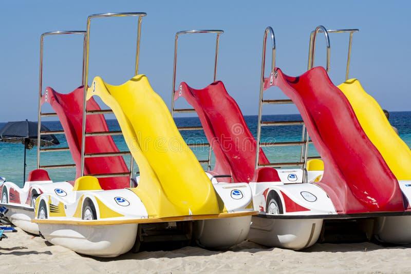 Bateaux color?s de p?dale avec des glissi?res pour le loyer sur la plage sablonneuse photos stock