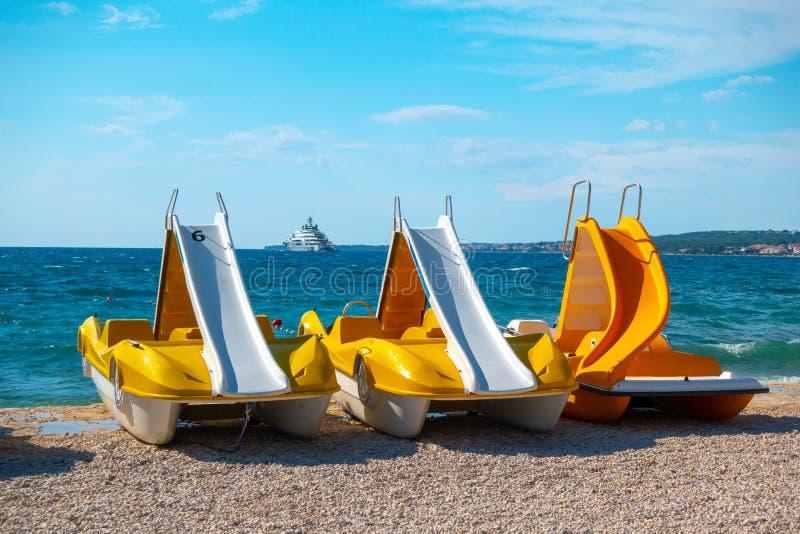 Bateaux colorés de pédale, pedolinos jaunes sur la plage photos stock