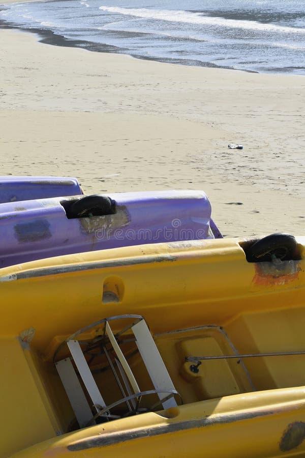 Bateaux colorés retournés de pédale sur la plage photos stock